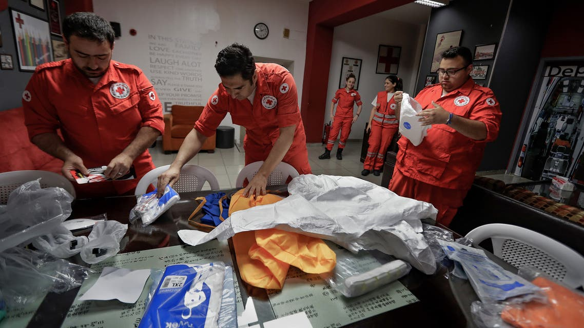 Members of the Lebanese Red Cross arrange their protective outfits in Beirut on May 29, 2020, during the novel coronavirus pandemic crisis. (AFP)