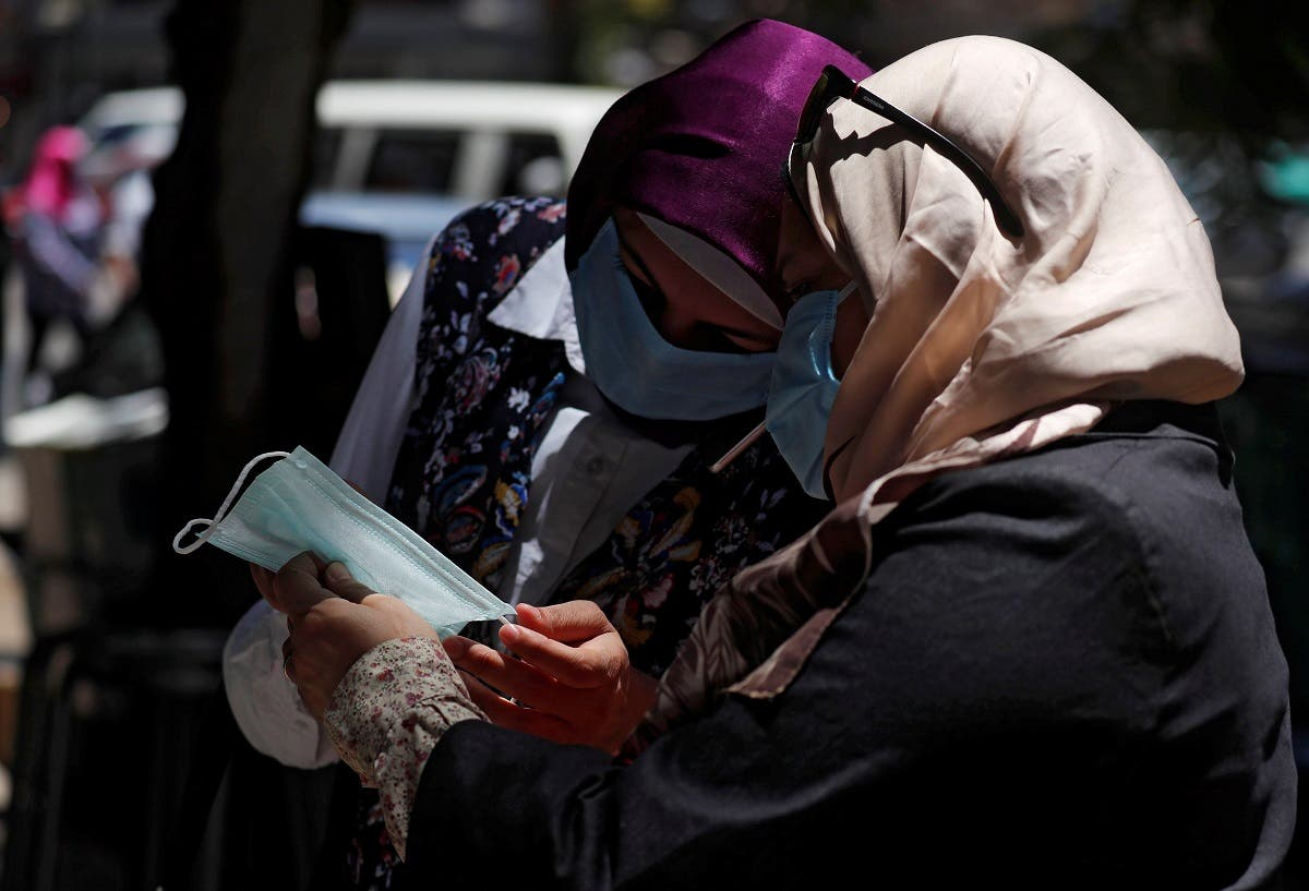 Women wearing face masks check a mask in front of a medical supplies shop in downtown Cairo, after Egypt's government made masks mandatory in public places and on public transport, in Cairo, Egypt on May 31, 2020. (Reuters)