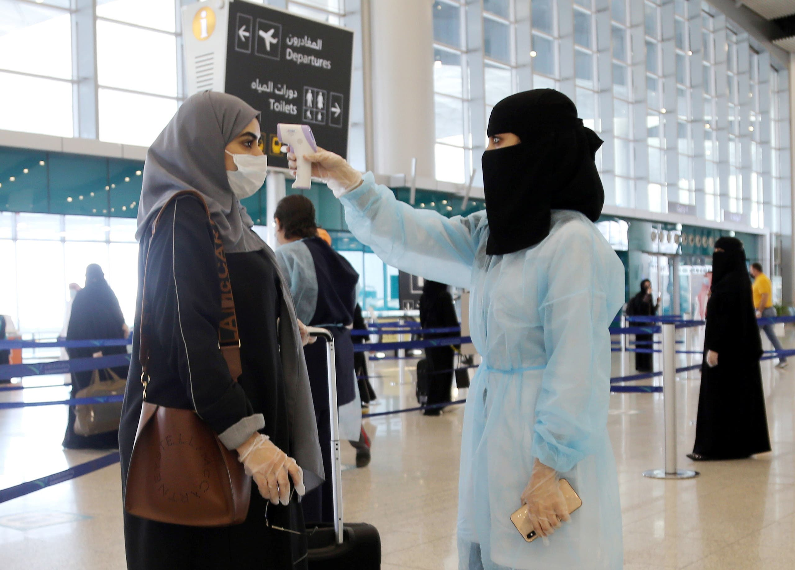 A security woman checks the temperature of a woman at Riyadh International Airport, after Saudi Arabia reopened domestic flights, following the outbreak of the coronavirus in Riyadh. (File photo: Reuters)
