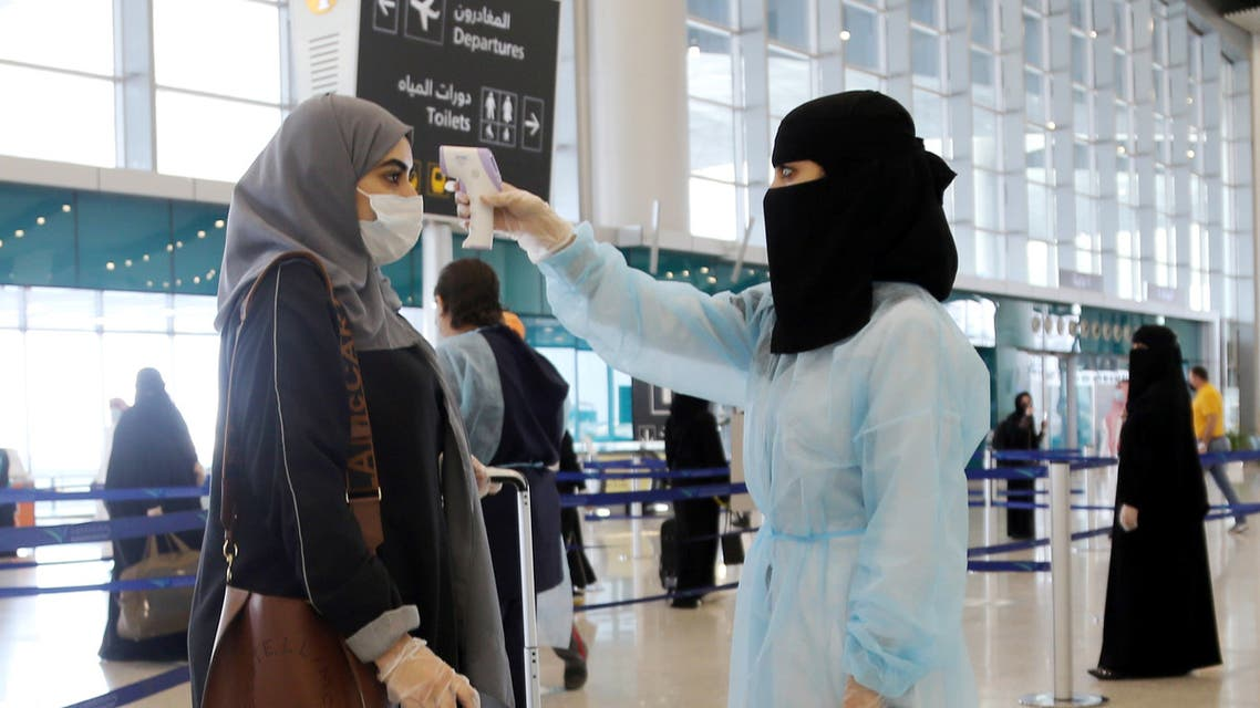 A security woman checks the temperature of a woman at Riyadh International Airport, after Saudi Arabia reopened domestic flights, following the outbreak of the coronavirus disease (COVID-19), in Riyadh, Saudi Arabia May 31, 2020. REUTERS/Ahmed Yosri