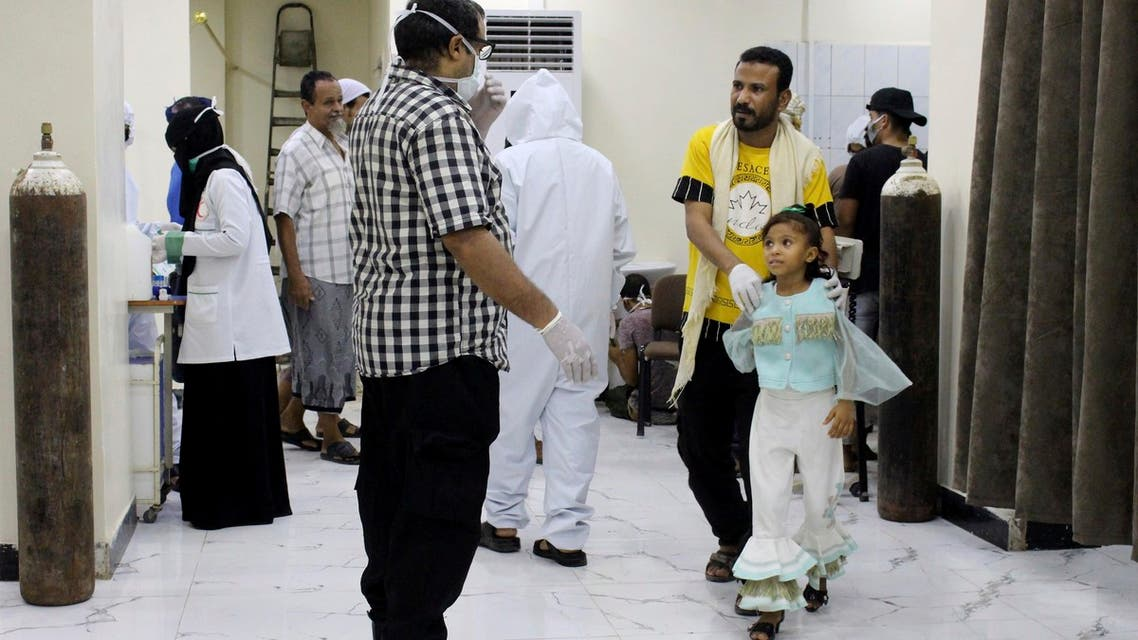 In this May 12, 2020 photo, Yemeni medical workers wearing masks and protective gear talk to patients at hospital in Aden, Yemen. People have been dying by the dozens each day in southern Yemen's main city, Aden, many of them with breathing difficulties, say city officials. Blinded with little capacity to test, health workers fear the coronavirus is running out of control, feeding off a civil war that has completely broken down the country. (AP Photo/Wail al-Qubaty)
