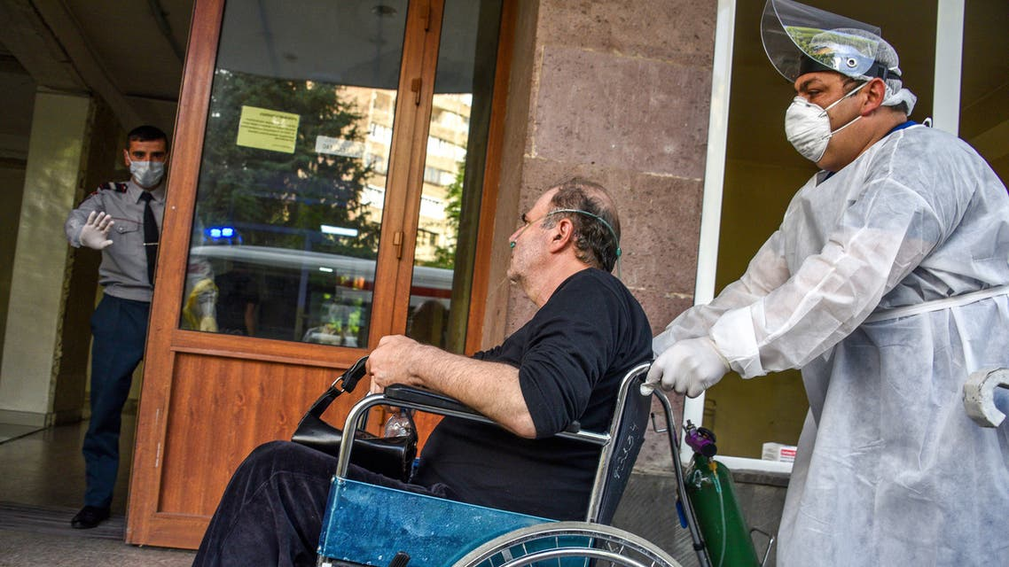 A hospital worker wearing a face mask and protective gear pushes a man in a wheelchair at the Grigor Lusavorich Medical Centre in Yerevan on May 29, 2020, amid the COVID-19 outbreak, caused by the novel coronavirus. Cases of the new coronavirus have overwhelmed Armenia's hospitals, officials said on May 27, raising the prospect that intensive care treatment could be restricted to patients with the best chance of survival. The tiny Caucasus nation of some three million has so far reported 7,774 coronavirus cases and 98 deaths.