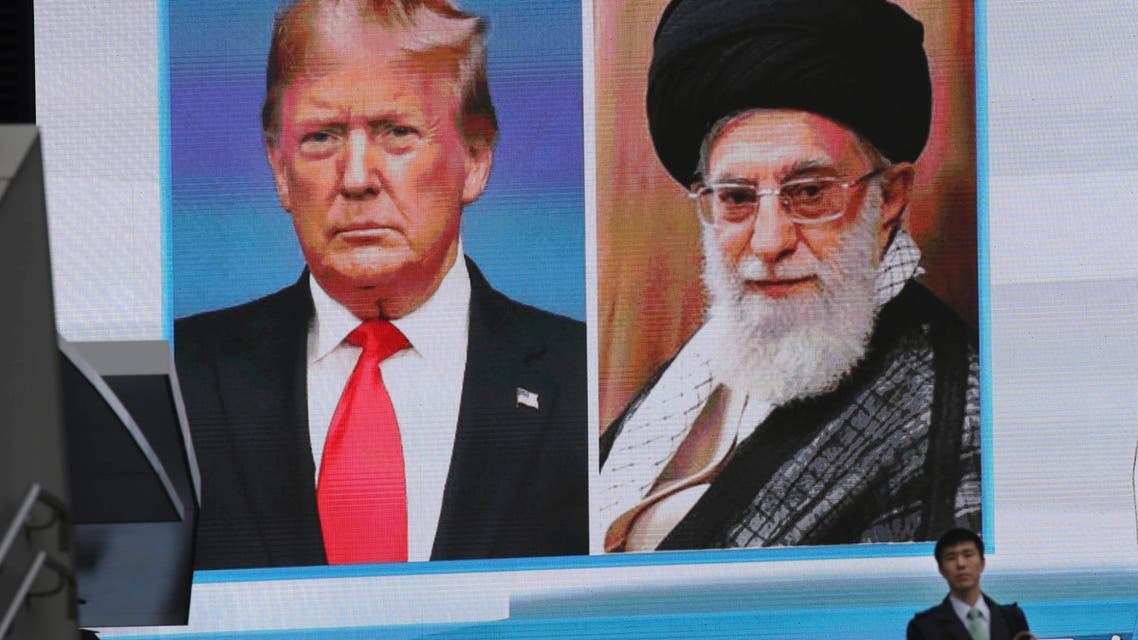 A man walks by a huge screen showing U.S. President Donald Trump, left, and Iranian Supreme Leader Ayatollah Ali Khamenei, in Tokyo, Wednesday, Jan. 8, 2020. (AP)