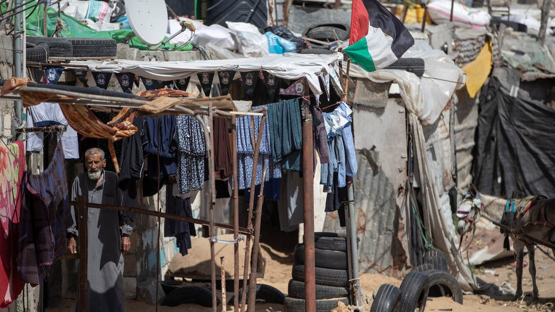 A Palestinian stands among hanging clothes in a slum on the outskirts of Khan Younis Refugee Camp, in the southern Gaza Strip on June 1, 2020. (AP)