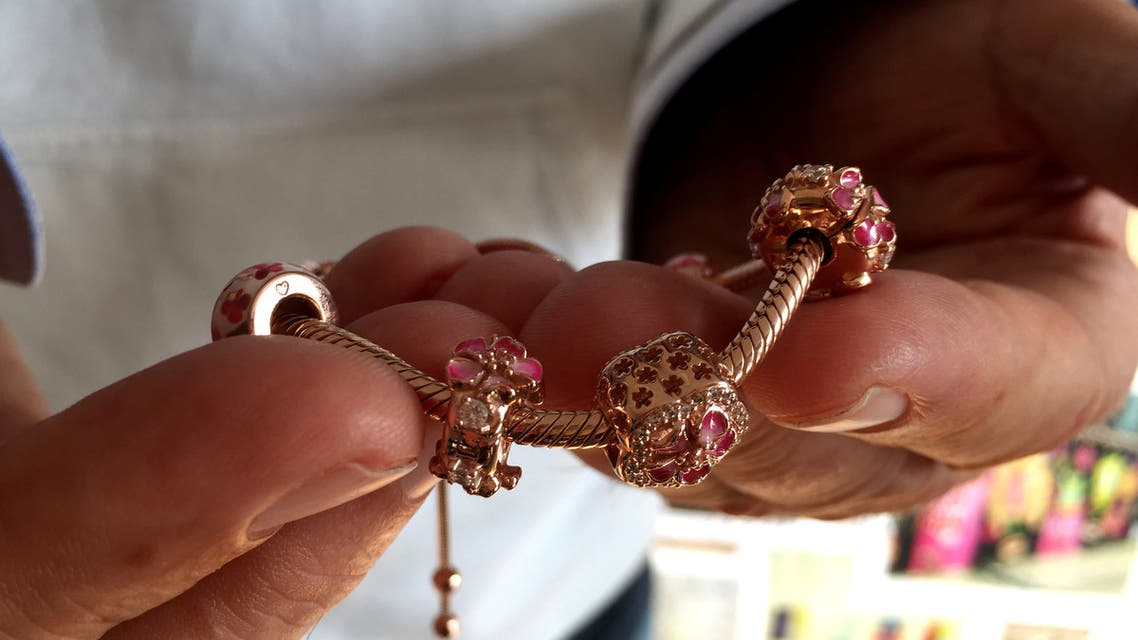 A Pandora employee shows a piece from the jewelry collection Peach Blossom, April 8, 2019. (File photo: Reuters)