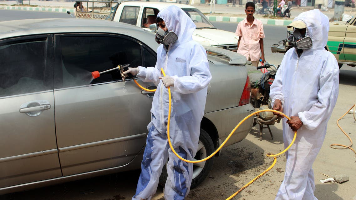 Yemeni sanitation workers, wearing protective gear, spray disinfectant in a neighbourhood in the northern Hajjah province on May 31, 2020, during the ongoing coronavirus pandemic. (AFP)