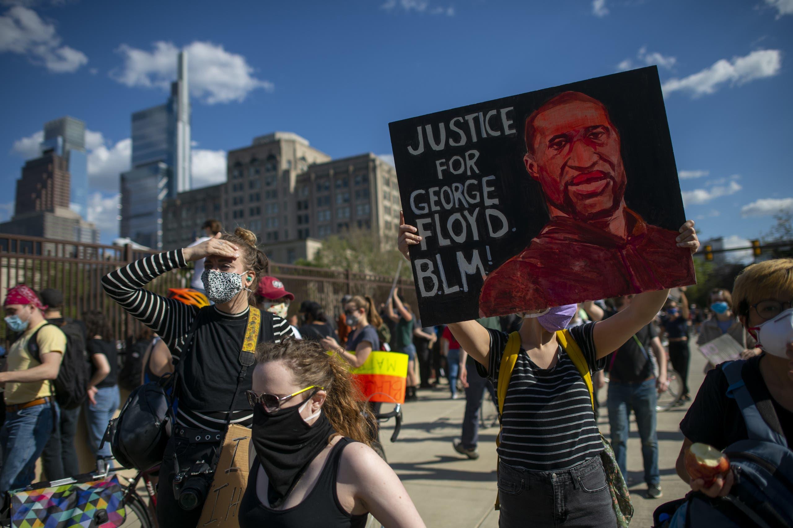 متظاهرون يحملون صورة فلويد (أرشيفية- فرانس برس)