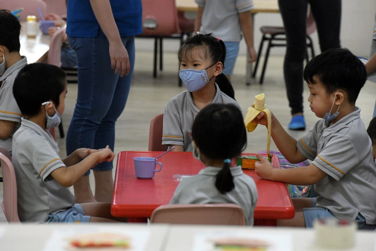 Pre-school children gather around a table inside their classroom as schools reopened in Singapore on June 2, 2020. (AFP)