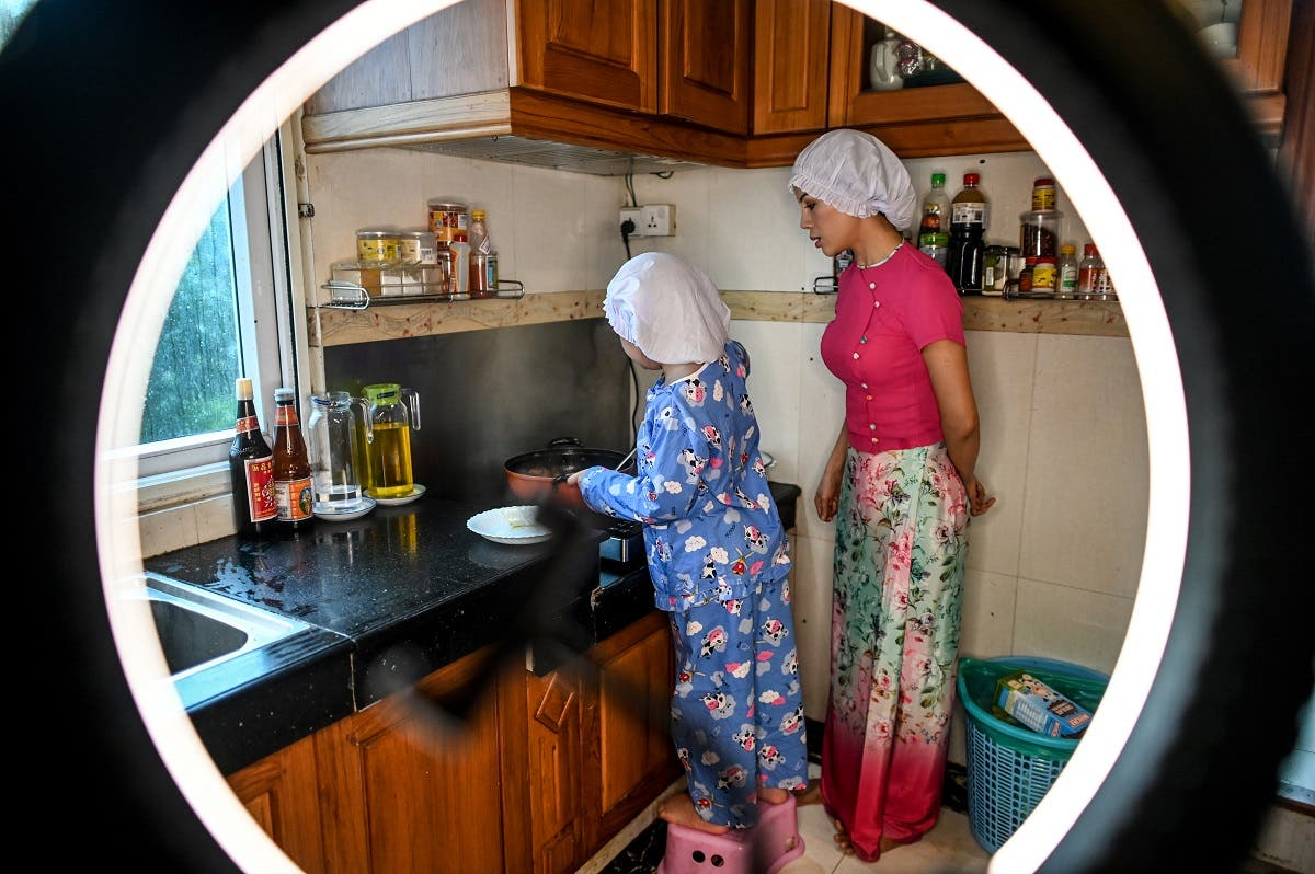Moe Myint May Thu (R) and her mother Honey Cho cooking while filming a video at their house in Yangon. (AFP)