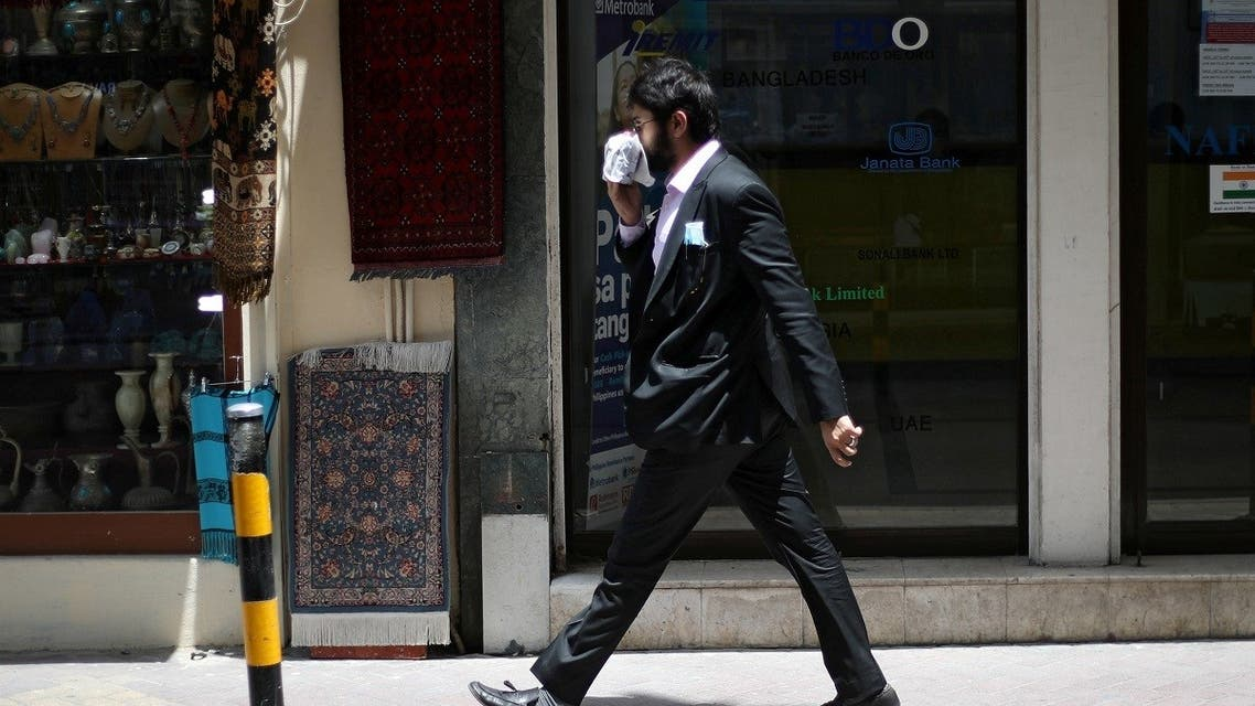A man uses a cloth as a face mask following the outbreak of Coronavirus disease (COVID-19), as he walks in a central souq ahead of the holy month of Ramadan in Manama, Bahrain, April 23, 2020. (Reuters)