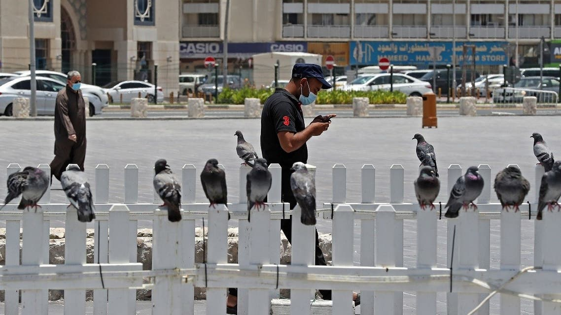 A man wearing a protective mask checks his phone as he walks by at Qatar's touristic Souq Waqif bazar in the capital Doha, on May 17, 2020. (AFP)