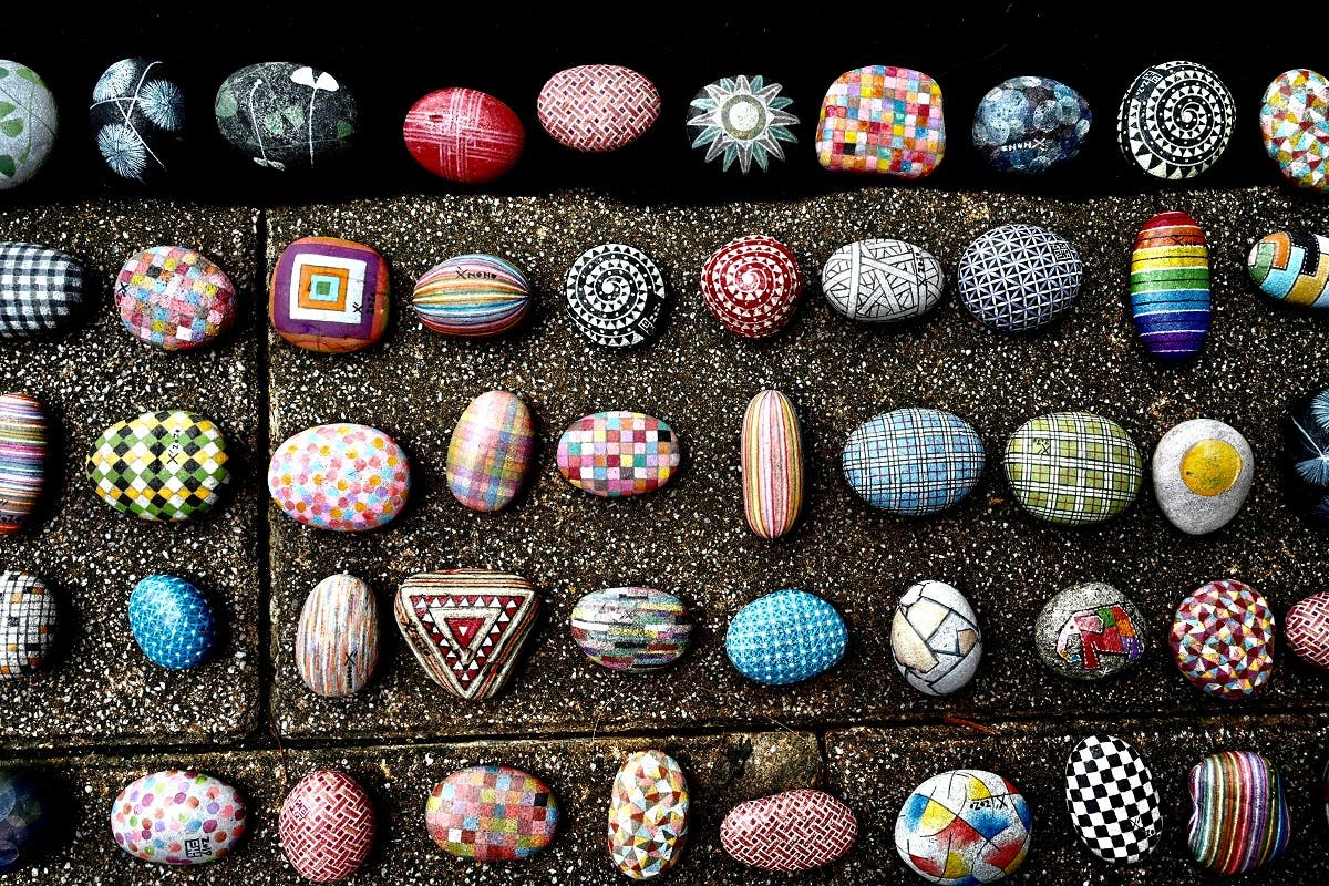 """colourfully painted stones painted by artist Wu Rong-bi, also as know as """"Uncle Stone,"""" on display along a street in Taipei. (AFP)"""