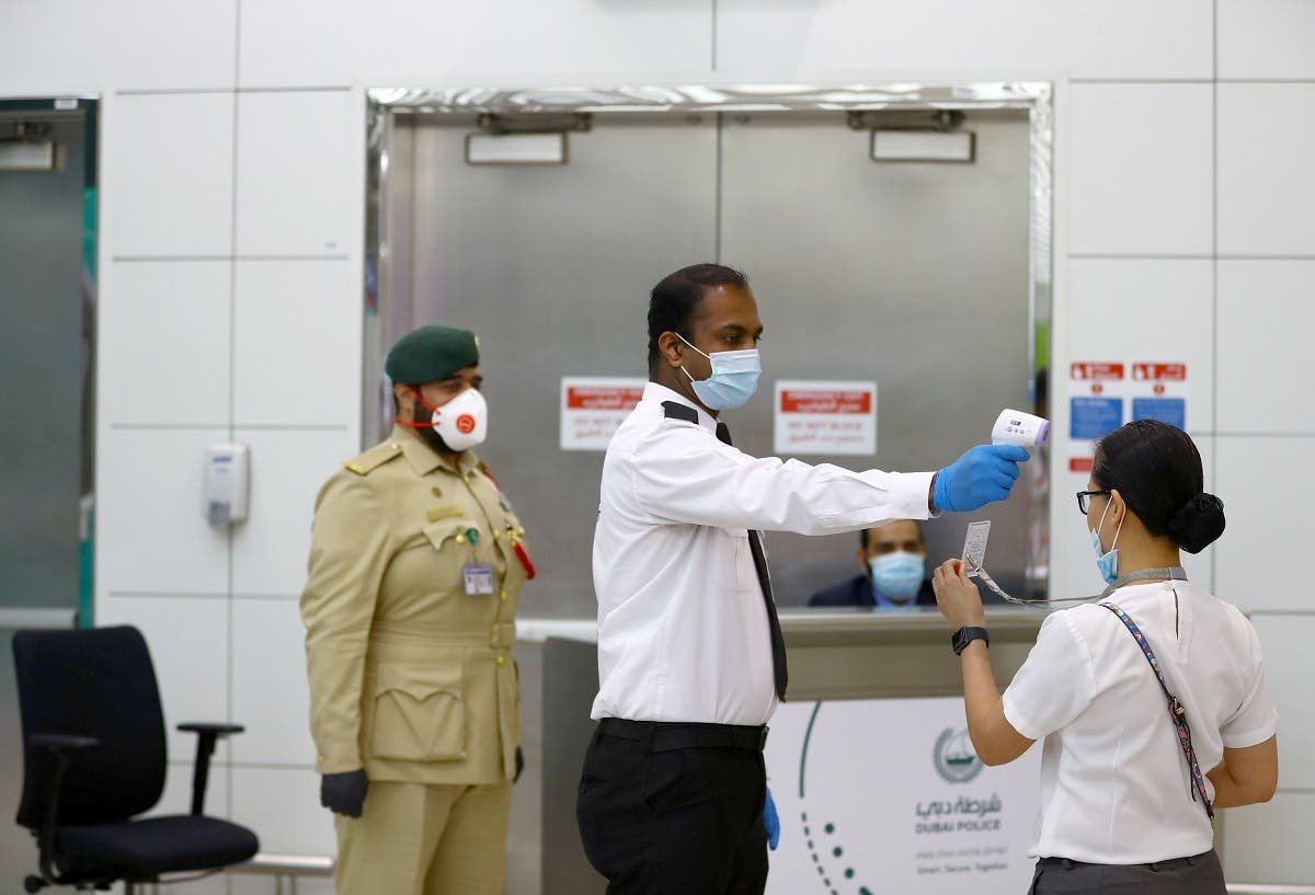 A security man takes temperature of a woman at Dubai International Airport. (File photo: Reuters)