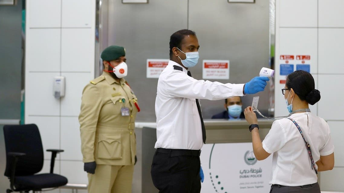 A security man takes temperature of a woman amid the outbreak of the coronavirus disease (COVID-19) at Dubai International Airport, UAE April 27, 2020. (Reuters)