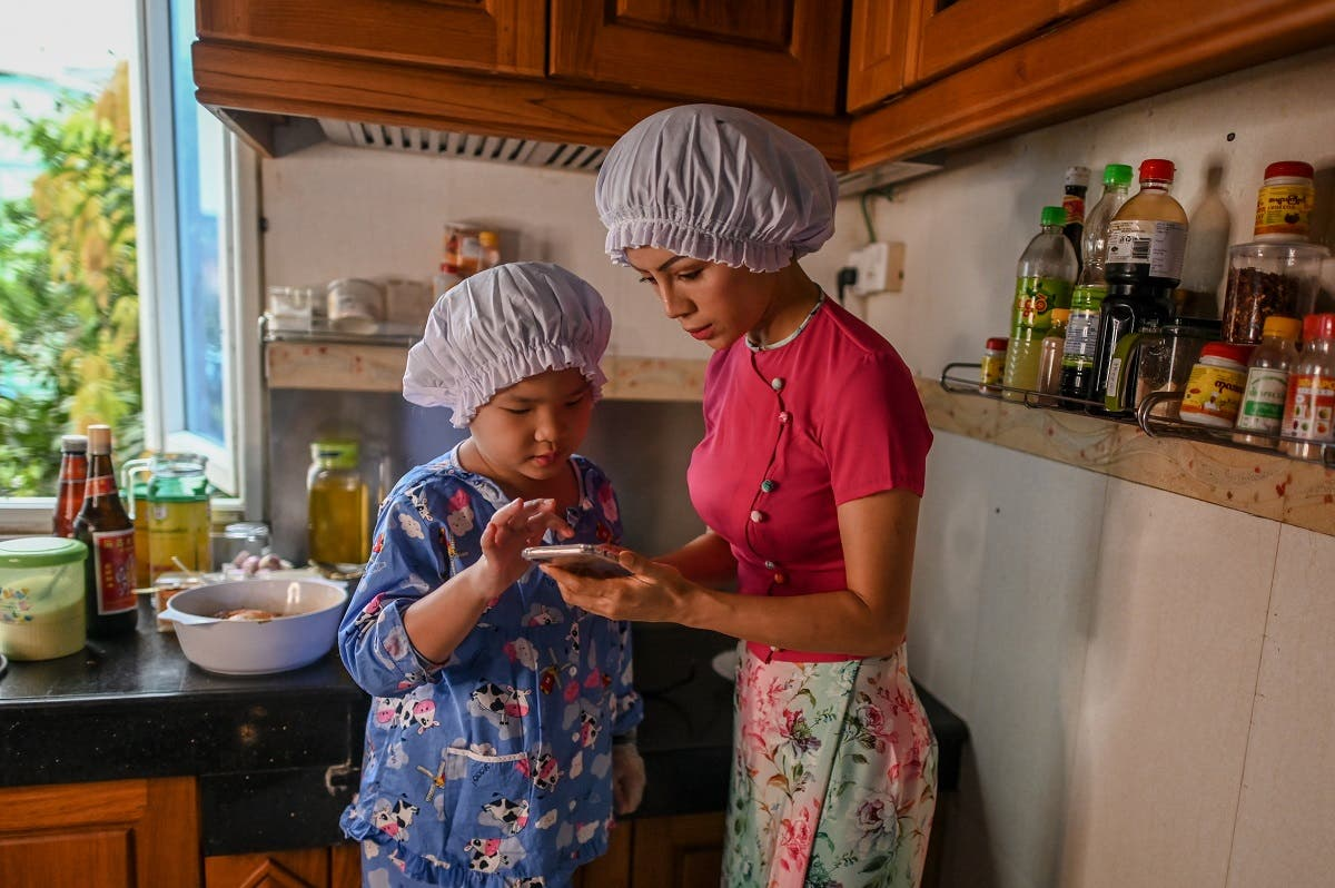 Moe Myint May Thu (L) and her mother Honey Cho filming a cooking video at their house in Yangon. (AFP)