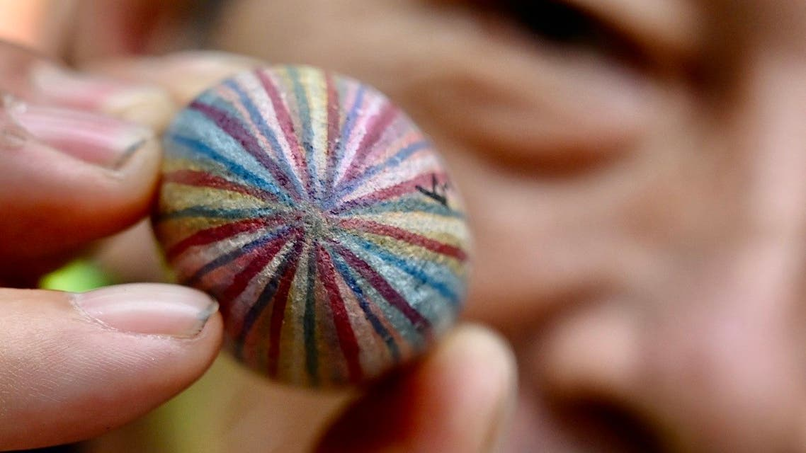 """artist Wu Rong-bi, also as know as """"Uncle Stone,"""" displaying a colourfully painted stone along a street in Taipei. (AFP)"""