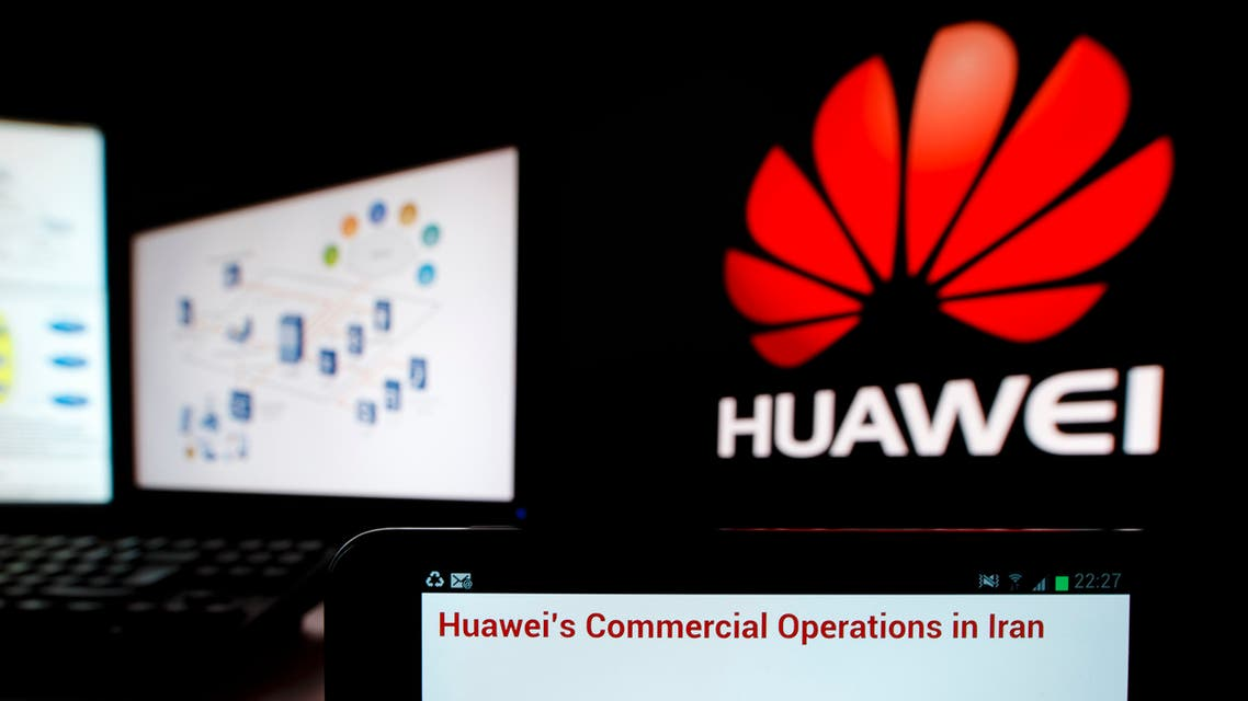 An excerpt of a statement from Chinese telecom equipment firm Huawei is displayed on a smartphone in front of computer screens showing the Huawei logo (R). (Reuters)