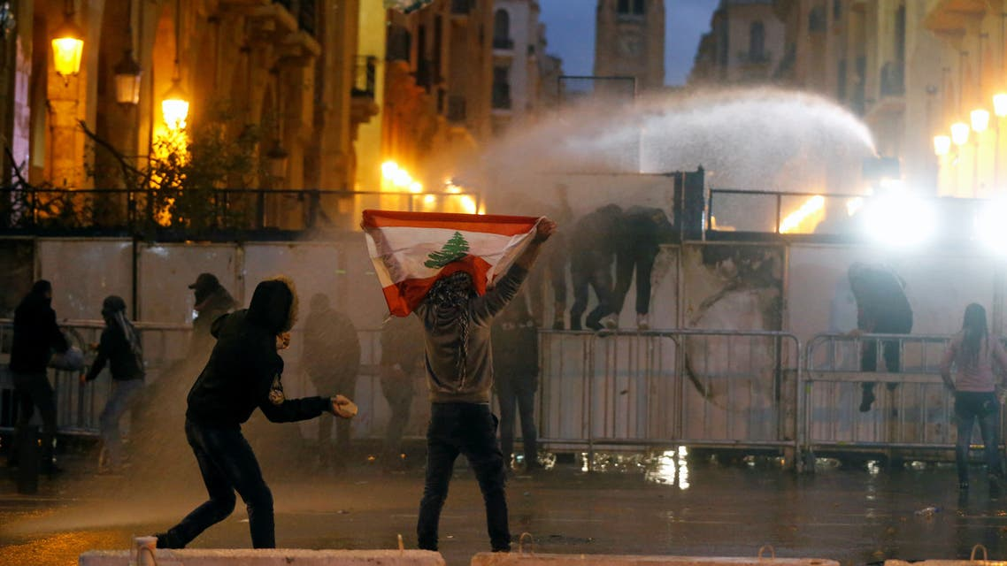 A demonstrator holds up a national flag as police use water cannon during a protest against the newly formed government in Beirut, Lebanon January 22, 2020. (Reuters)