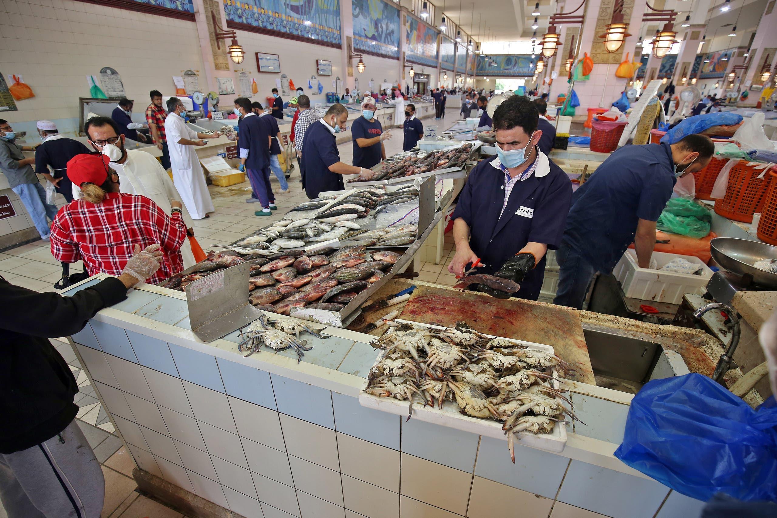 كمامات للوقاية من كورونا داخل سوق للأسماك في الكويت