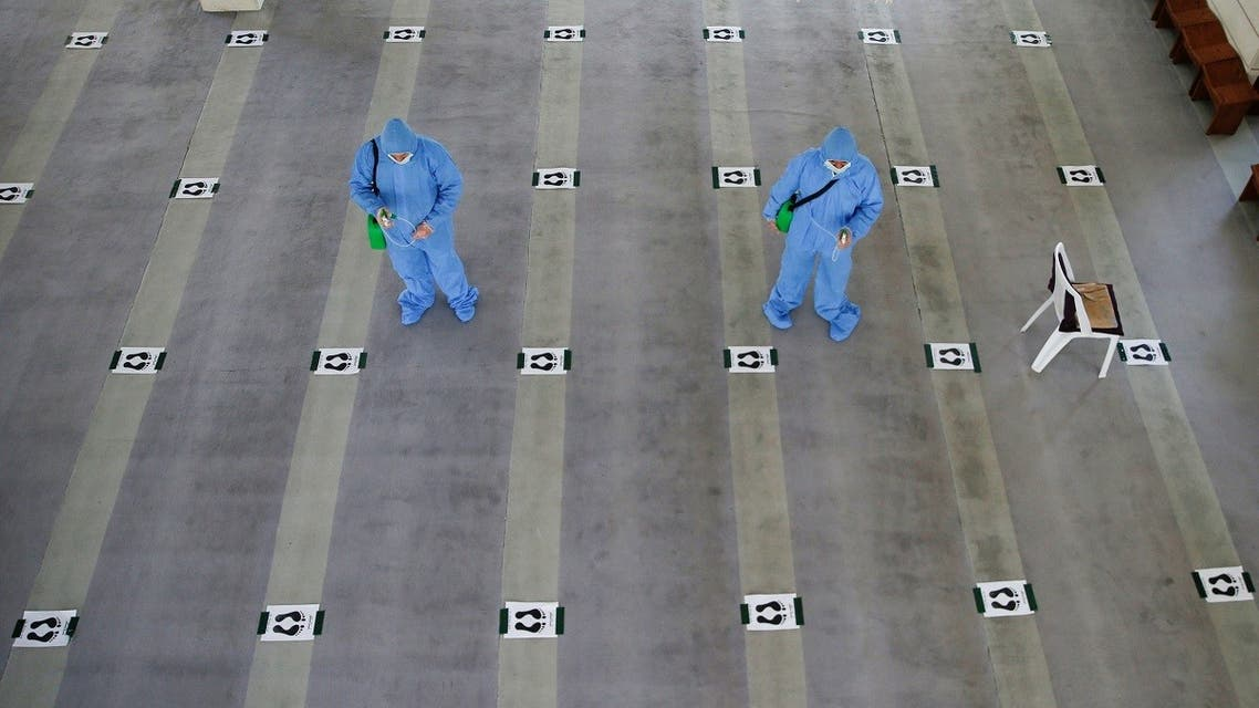 Workers, wearing protective suits, spray disinfectant in a mosque to prevent the spread of the coronavirus disease (COVID-19) in Amman. (Reuters)