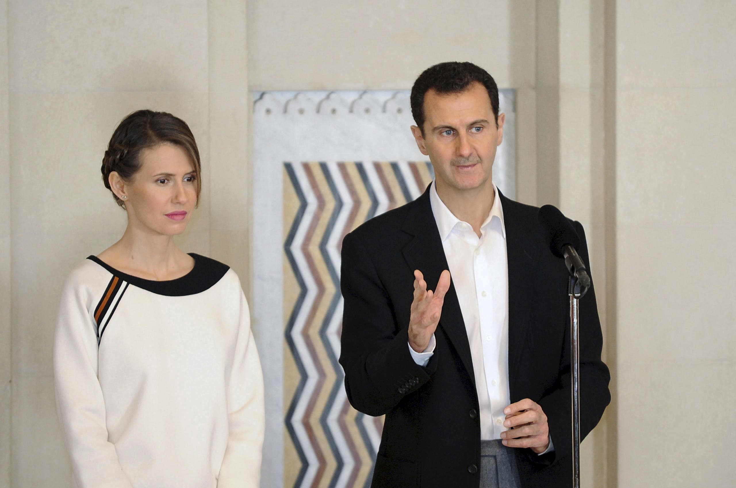 Syria's President Bashar al-Assad stands next to his wife Asma, as he addresses injured soldiers and their mothers during a celebration marking Syrian Mother's Day in Damascus, in this handout picture provided by SANA on March 21, 2016. (Reuters)