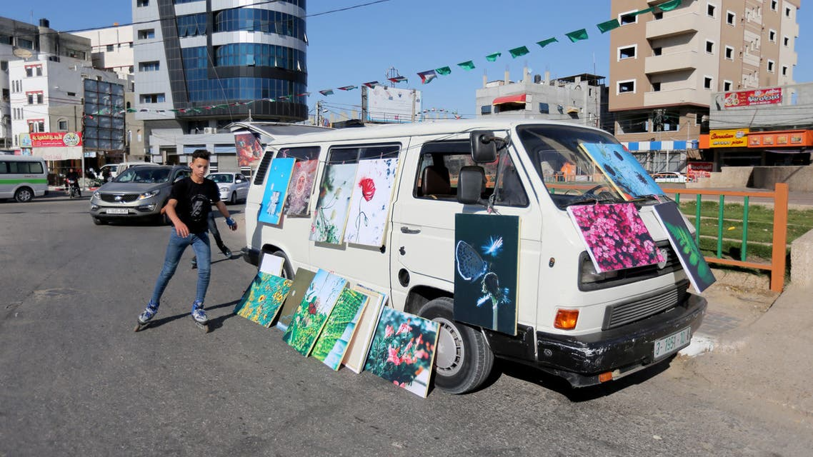 A boy rollerblades past an art-van with paintings put on sale by Palestinian artists, amid the coronavirus disease (COVID-19) spread, in the southern Gaza Strip May 30, 2020. (Reuters)