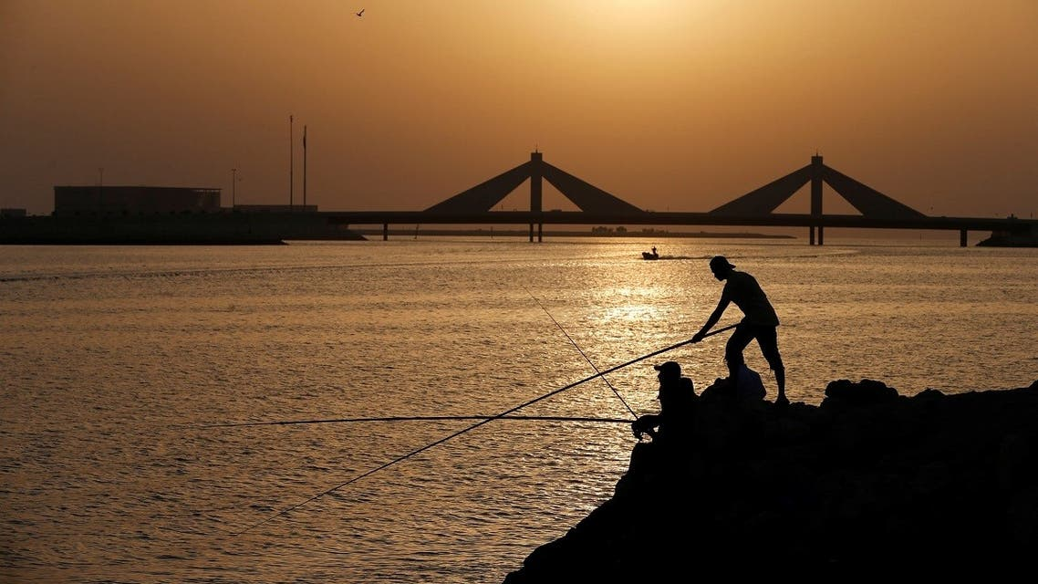 People fish during the sun set, following the outbreak of the coronavirus disease (COVID-19), in Manama. (Reuters)