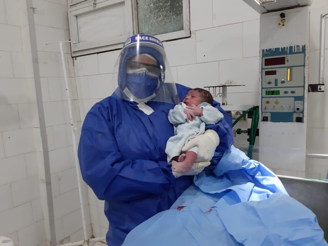 أحد أعاضاء الطاقم الطبي مع الطفل