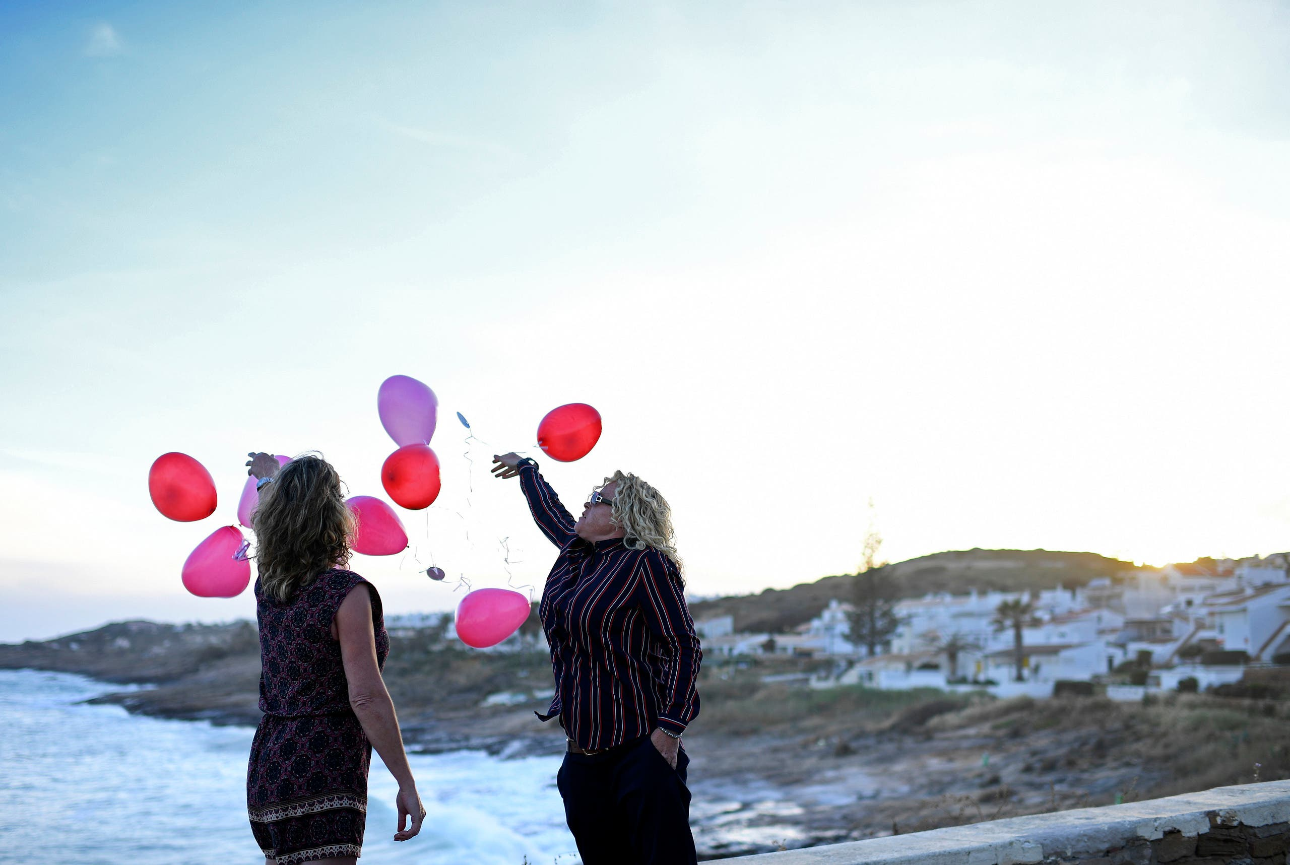 Two people release baloons in Praia da Luz, near Lagos, to mark the 10th anniversary of the dissapearance of British child Madeleine McCann on May 3, 2017. (AFP)