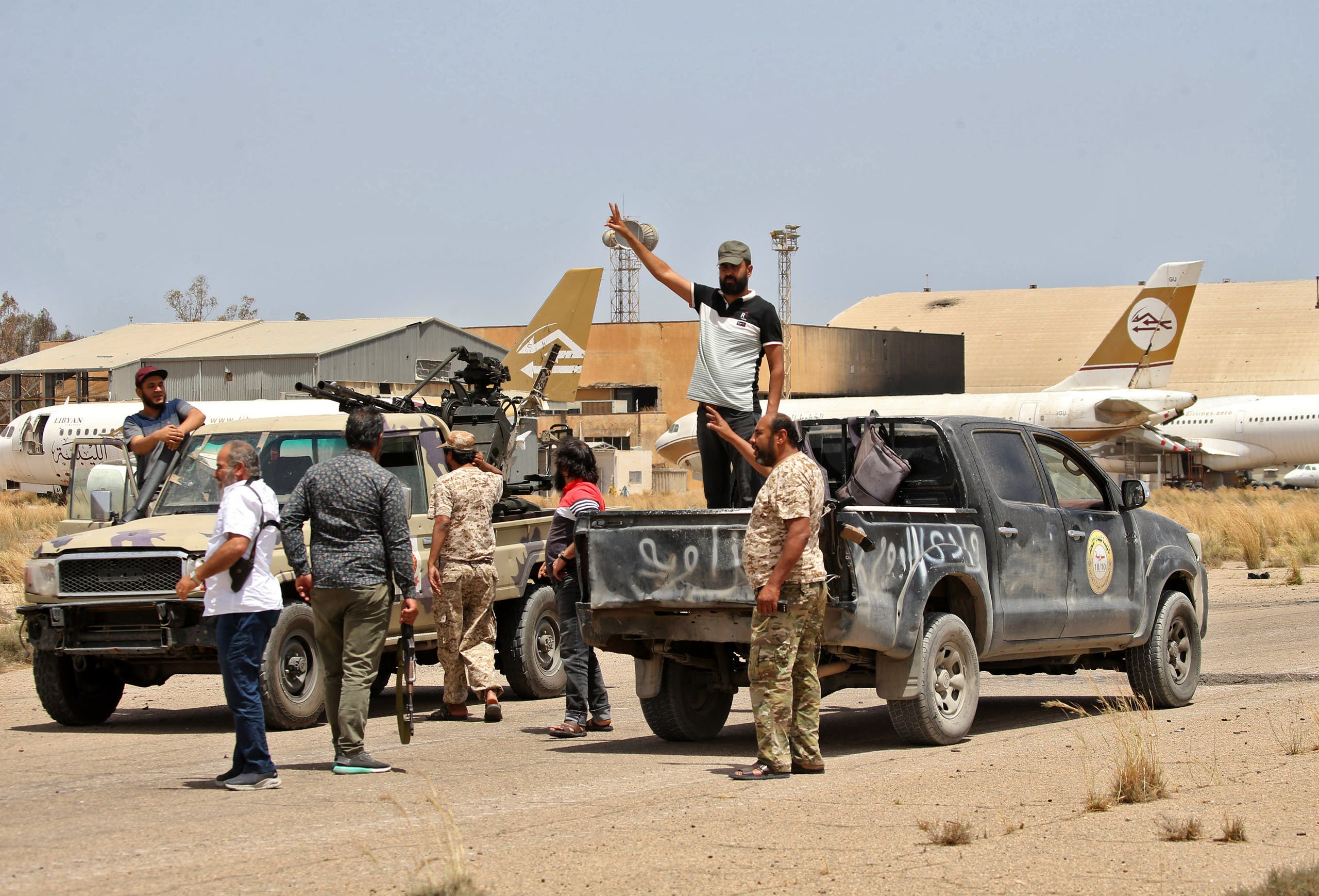 Fighters loyal to the UN-recognised Libyan Government of National Accord (GNA) stand outside a technical (pickup truck mounted with turret) at Tripoli International Airport. (Reuters)