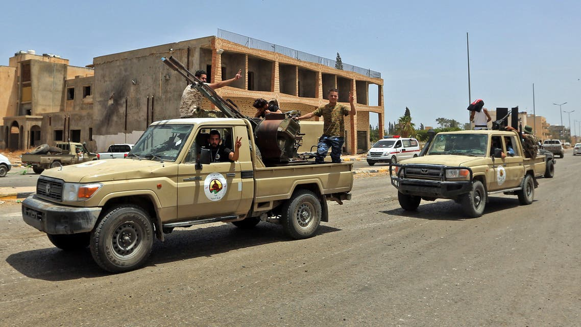 Fighters loyal to the UN-recognised Libyan Government of National Accord (GNA) stand outside a technical (pickup truck mounted with turret) at Tripoli International Airport, on the southern outskirts of the Libyan capital Tripoli on June 4, 2020, after the complex was taken over by pro-GNA forces following clashes with rival forces loyal to strongman Khalifa Haftar. The GNA said on June 4 that it was back in full control of the capital and its suburbs after more than a year of fighting off an offensive by eastern strongman Khalifa Haftar. The announcement came after GNA forces retook the capital's civilian airport the previous day, more than a year after losing it in Haftar's initial drive on the capital.