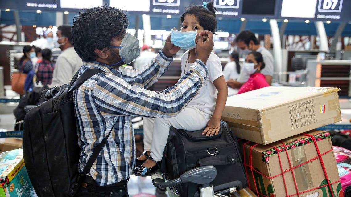 Members of an Indian family check in at the Muscat International Airport before leaving the Omani capital on a flight to return to their country, on May 9, 2020, amid the novel coronvirus pandemic crisis. India has been bringing home hundreds of thousands of its citizens stuck abroad after it banned all incoming international flights in late March in a bid to control the coronavirus crisis, leaving vast numbers of workers and students stranded.