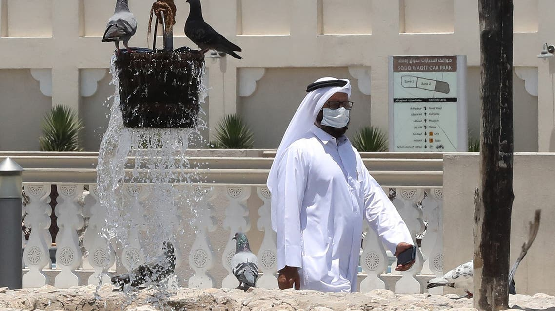 A man wearing a ptotective mask walks by a water fountain at Qatar's touristic Souq Waqif bazar in the capital Doha, on May 17, 2020, as the country begins enforcing the world's toughest penalties for failing to wear masks in public while it battles one of the world's highest coronavirus infection rates. More than 30,000 people have tested positive for COVID-19 in the tiny Gulf country, 1.1 percent of the 2.75 million population, although just 15 people have died. Violators of the new rules will face up to three years in jail and fines of as much as $55,000.