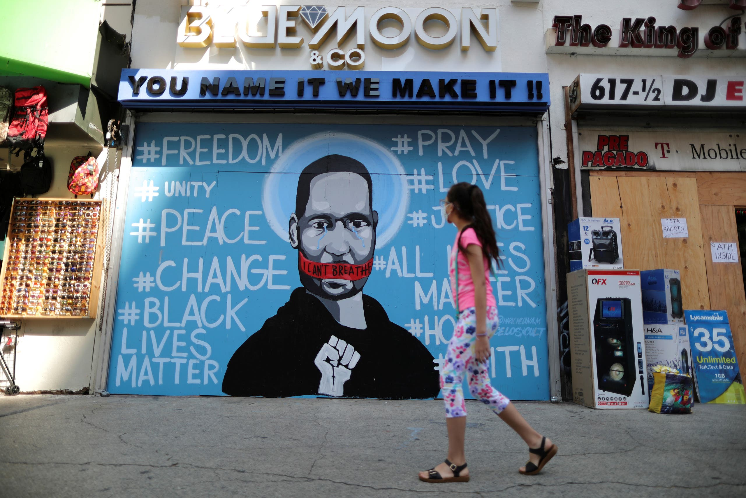 A girl walks past a mural commemorating George Floyd, in downtown Los Angeles, California, U.S. June 4, 2020. (Reuters)