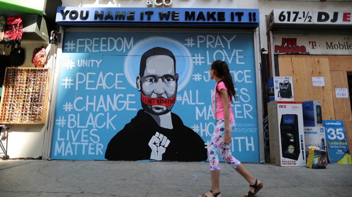 A girl walks past a mural commemorating George Floyd, in downtown Los Angeles, California, U.S. June 4, 2020. (Reuters)