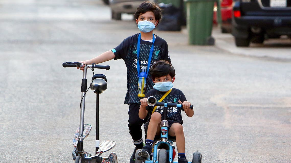 Kuwaiti children, wearing protective facemasks due to the coronavirus pandemic, cycle in a street in the Salwa district of Kuwait City on May 29, 2020.