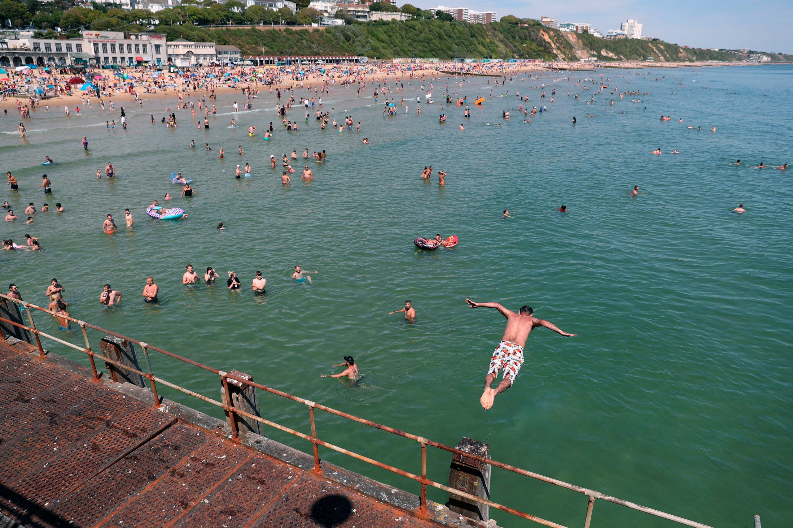 A swimmer jumps into the sea at Bournemouth Beach in Bournemouth, England on June 2, 2020. (AP)