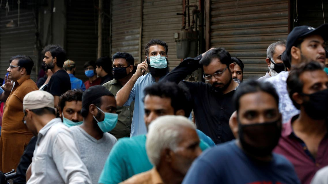 Shopkeepers stand outside a shopping bazar, after police sealed it for not following the government's precautionary measures following the spread of coronavirus disease (COVID-19). (Reuters)
