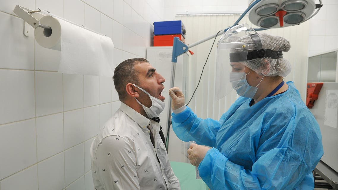 A medical specialist wearing protective gear takes a swab from a man at Sheremetyevo International Airport amid the outbreak of the coronavirus disease (COVID-19) outside Moscow, Russia June 4, 2020. Alexander Avilov/Moscow News Agency/Handout via REUTERS ATTENTION EDITORS - THIS IMAGE HAS BEEN SUPPLIED BY A THIRD PARTY. MANDATORY CREDIT.