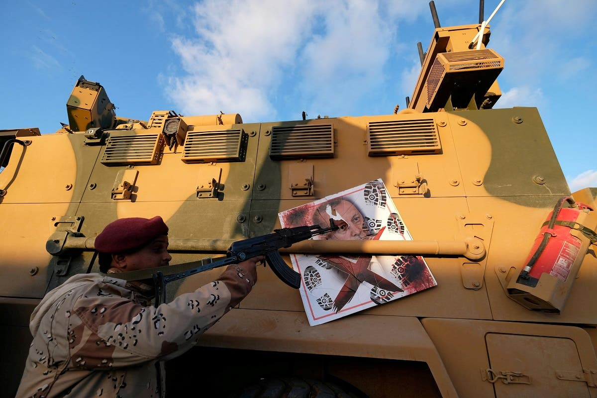 A member of Libyan National Army (LNA) commanded by Khalifa Haftar, points his gun to the image of Turkish President Tayyip Erdogan hanged on a Turkish military armored vehicle, which LNA said they confiscated during Tripoli clashes, in Benghaz. (Reuters)