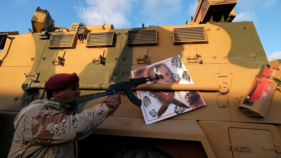 A member of the LNA points his gun to the image of Turkish President Tayyip Erdogan on a Turkish military armored vehicle. (File Photo: Reuters)