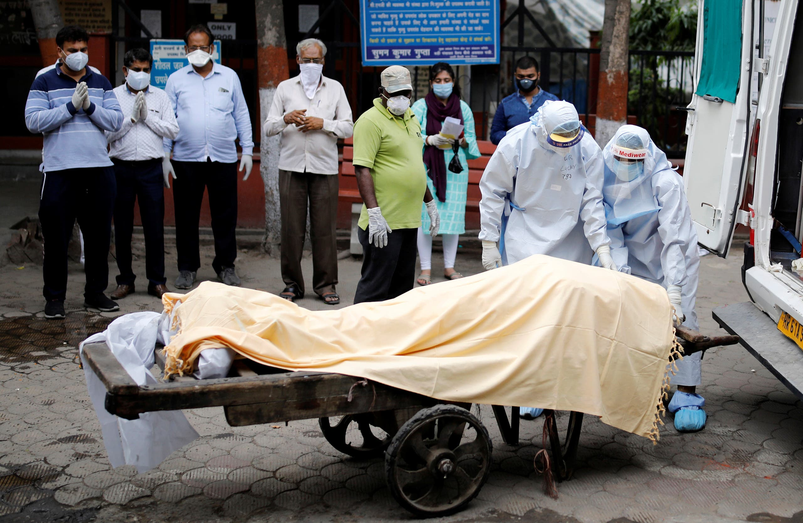 Health workers cover the body of a man who died due to the coronavirus disease (COVID-19), as relatives pay their respects, at a crematorium in New Delhi, India, June 4, 2020. (Reuters)