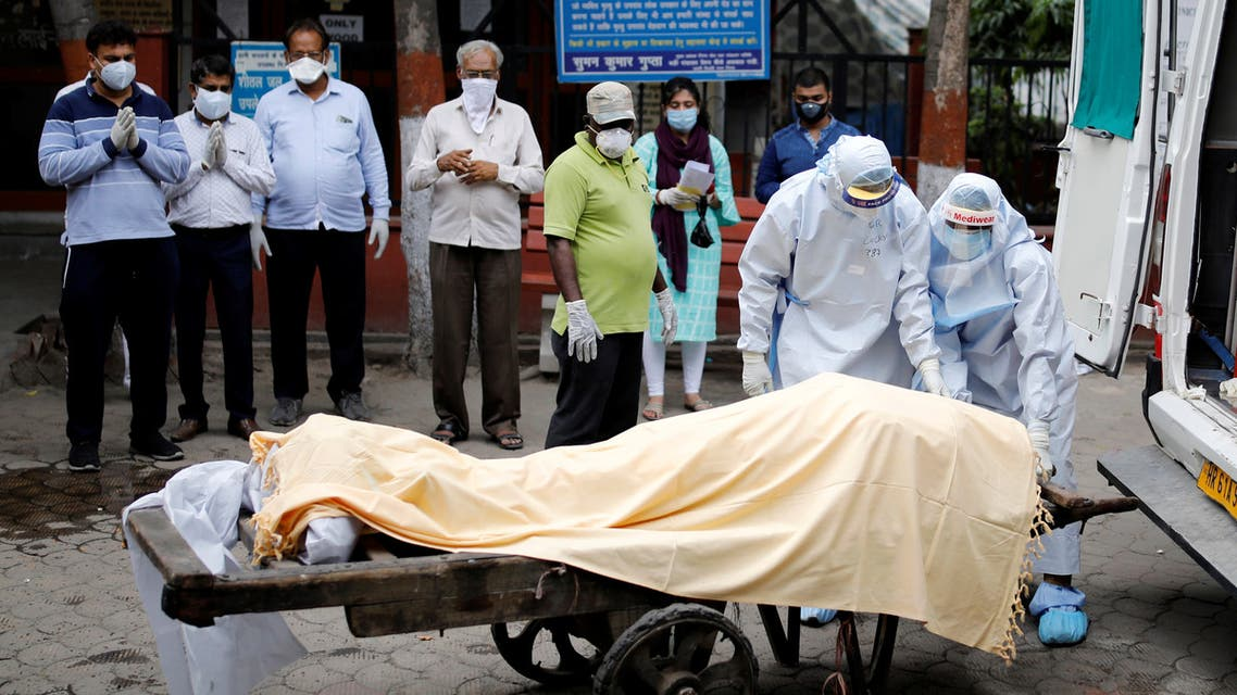 Health workers cover the body of a man who died due to the coronavirus disease (COVID-19), as relatives pay their respects, at a crematorium in New Delhi, India, June 4, 2020. REUTERS/Adnan Abidi