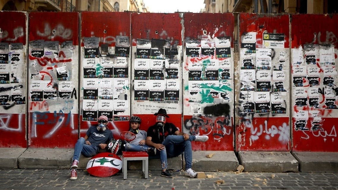 Lebanese protesters sit outside a fortified entrance of the Lebanese parliament during a demonstration in central Beirut on June 6, 2020. (AFP)
