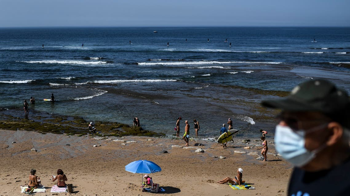 A man wearing a face mask walks past people enjoying a day at Parede beach in Cascais in the outskirts of Lisbon on May 26, 2020 as temperatures rise and the Portuguese government loosens a lockdown put in place to slow the spread of the novel coronavirus.