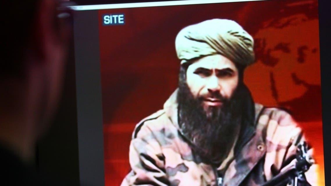 A man looks at a picture of Abdelmalek Droukdel, aka Abu Musab Abdul Wadud, head of Al-Qaeda in the Islamic Maghreb (AQIM) seen on US monitoring group SITE Intelligence. (AFP)