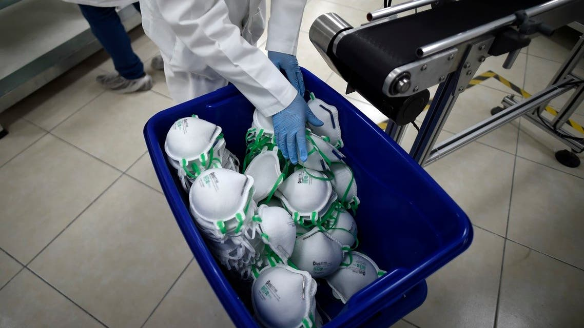 An employee arranges N95 face masks in a box, at a factory that produces 40,000 N95 masks per day, in Mexico City. (AFP)
