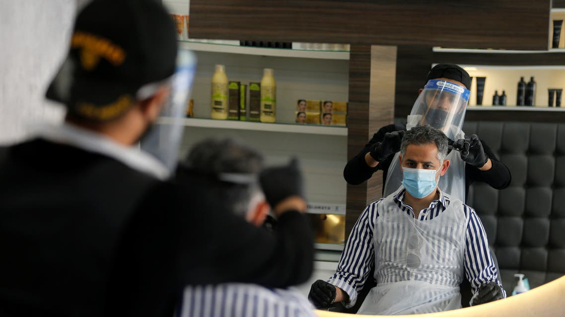 A barber wears a protective face shield and gloves as he cuts hair of a customer at a local barber shop after its reopening, following the outbreak of the coronavirus disease (COVID-19), in Isa Town, Bahrain May 27, 2020. REUTERS/Hamad I Mohammed