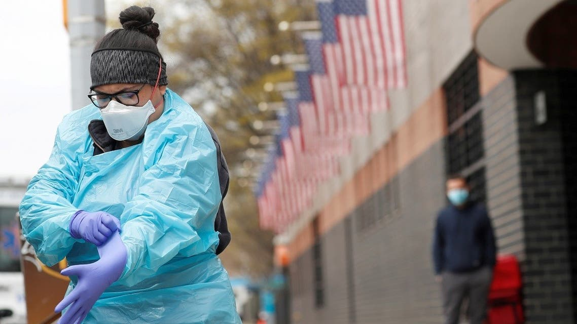 An Emergency Medical Technician (EMT) dons personal protective equipment before going into Elmhurst Hospital during the ongoing outbreak of the coronavirus disease (COVID-19) in the Queens borough of New York. (Reuters)