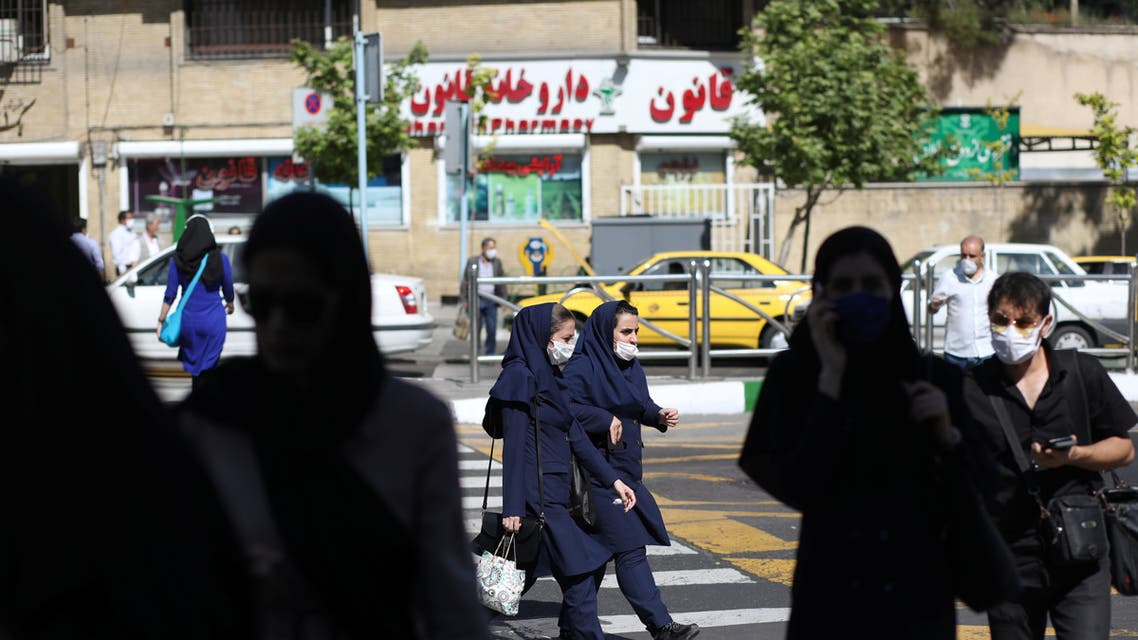 Iranian people wear protective face masks and gloves, following the outbreak of the coronavirus disease (COVID-19), as they walk in Vali-E-Asr street, in Tehran. (Reuters)